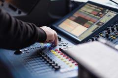 Las manos del ingeniero de sonido en la consola de mezcla fotografía de archivo libre de regalías