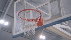 Las manos del jugador de básquet lanzar la bola en la cesta, va a través Jugador del juego de baloncesto profesional en la acción almacen de video