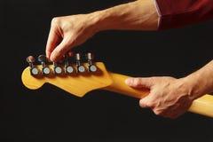 Las manos del músico adaptan la guitarra eléctrica en fondo negro Imagen de archivo libre de regalías