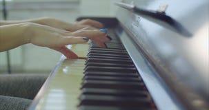 Las manos del músico que juegan en el teclado de piano metrajes