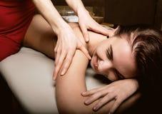 Las manos del masajista del primer que hacen masaje de la vuelta, paciente relajado gozan foto de archivo libre de regalías