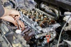Las manos del mecánico aprietan la nuez con la llave Imagen de archivo libre de regalías