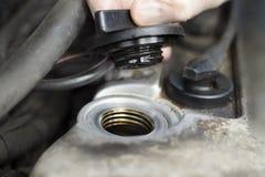 Las manos del mecánico de coche desatornillan el casquillo del llenador del aceite Imagenes de archivo
