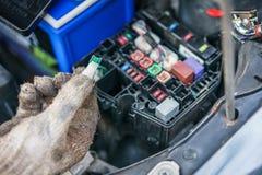 Las manos del mecánico que substituye el fusible en el coche El mecánico selecciona el fusible correcto Foco selectivo foto de archivo libre de regalías