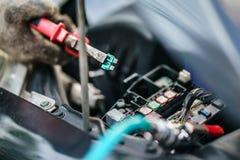 Las manos del mecánico que substituye el fusible en el coche El mecánico selecciona el fusible correcto Foco selectivo foto de archivo