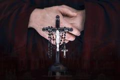 Las manos del monje del misterio con un cabo, crucifijo y un rosario negro Imagen de archivo