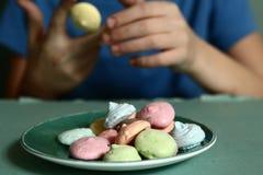 Las manos del muchacho con las galletas del macaron se cierran para arriba Fotos de archivo