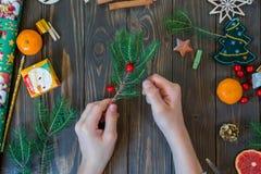 Las manos del muchacho cortaron la cinta roja en el fondo de madera decoración de la guirnalda del Año Nuevo imagen de archivo