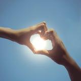 Las manos del muchacho y de la muchacha del adolescente en forma del corazón aman en cielo azul Fotografía de archivo