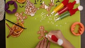 Las manos del niño adornan al hombre de pan de jengibre almacen de metraje de vídeo