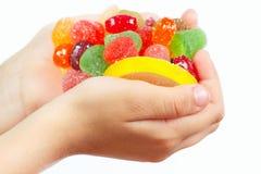 Las manos del niño con los caramelos y los dulces coloridos se cierran para arriba Imagen de archivo