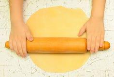 Las manos del niño desarrollan la pasta en la tabla Imagen de archivo