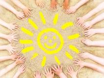 Las manos del niño enmarcan un sol sonriente amarillo foto de archivo libre de regalías