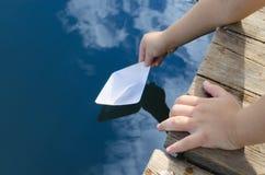 Las manos del niño pequeño, lanzamientos en el agua empapelan el barco con el embarcadero de madera Foto de archivo