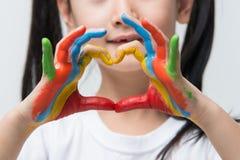 Las manos del niño pintadas hacen una forma del corazón imagenes de archivo