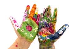 Las manos del niño pintaron la acuarela en el fondo blanco Foto de archivo