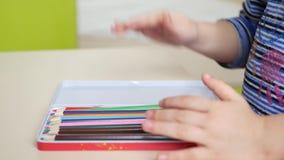 Las manos del niño ponen los lápices coloreados en la caja Primer almacen de metraje de vídeo