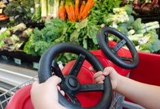Las manos del niño que conducen el carro de la compra Foto de archivo libre de regalías