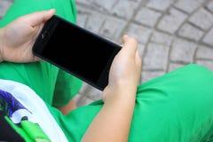 Las manos del niño sostienen el teléfono elegante para jugar y la educación foto de archivo