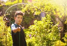 Las manos del niño sostienen la manguera con arrojar a chorros el agua en el jardín verde soleado del verano Fotografía de archivo libre de regalías