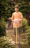 Las manos del niño sostienen la manguera con arrojar a chorros el agua en el jardín verde soleado del verano Imágenes de archivo libres de regalías