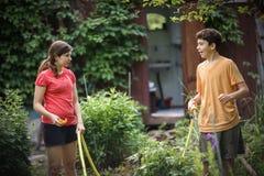 Las manos del niño sostienen la manguera con arrojar a chorros el agua en el jardín verde soleado del verano Fotografía de archivo