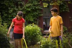 Las manos del niño sostienen la manguera con arrojar a chorros el agua en el jardín verde soleado del verano Fotos de archivo libres de regalías