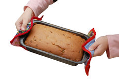 Las manos del niño sostienen una cacerola con la torta cocida al horno Fotos de archivo libres de regalías