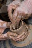 las manos del niño y del adulto moldearon el vesse de cerámica Fotografía de archivo libre de regalías