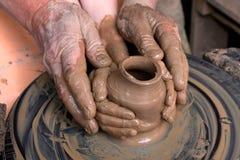 las manos del niño y del adulto moldearon el vesse de cerámica Fotos de archivo