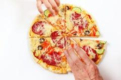 Las manos del niño y del adulto toman pedazos de pizza sabrosa Fotografía de archivo