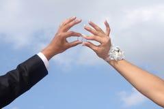 Las manos del novio y de la novia llevan a cabo los anillos de bodas. Imagenes de archivo