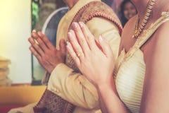 Las manos del novio y de la novia tailandeses ruegan al monje Imagen de archivo libre de regalías