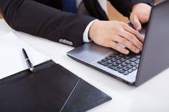 Las manos del oficinista que mecanografían en el ordenador portátil Imagen de archivo