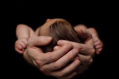 Las manos del padre que cuida - papá y recién nacido Imagenes de archivo