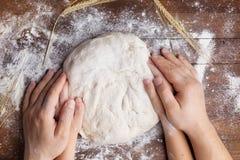 Las manos del padre y del niño preparan la pasta con la harina en la opinión de sobremesa de madera Pasteles hechos en casa para  fotografía de archivo