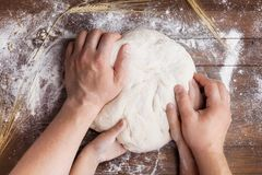 Las manos del padre y del niño preparan la pasta con la harina en la tabla de madera desde arriba Pasteles hechos en casa para el fotos de archivo