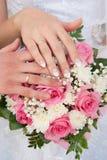 Las manos del par con los anillos de bodas encendido Fotos de archivo