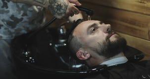Las manos del peluquero vierten el agua a un pelo del ` s del cliente almacen de video