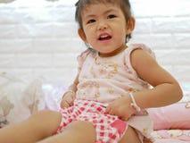 Las manos del peque?o beb? asi?tico que levantan los pantalones cortos, como ella que aprende ponerlo sola foto de archivo libre de regalías