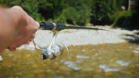 Las manos del pescador con el giro, pescando cerca de un pequeño río de la montaña almacen de video