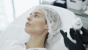 Las manos del primer de la cámara lenta del cosmetólogo en guantes pusieron el gel especial en cara paciente antes del tratamient almacen de metraje de vídeo