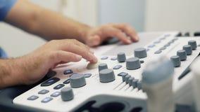 Las manos del primer de los trabajos del doctor con el escáner del ultrasonido, presionan los botones en la herramienta de diagnó almacen de metraje de vídeo