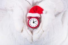 Las manos del primer en blanco hicieron punto las manoplas que sostenían el despertador rojo en el pequeño sombrero de santa foto de archivo libre de regalías