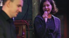 Las manos del primer del músico que realiza una melodía en el sintetizador y de un solista de la mujer joven que cantan una canci almacen de metraje de vídeo