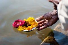 Las manos del rezo que salen de la flor ofrecen en el río Foto de archivo libre de regalías
