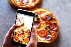 Las manos del ` s del adolescente con smartphone toman la imagen de la pizza hecha en casa Imagen de archivo