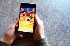 Las manos del ` s del adolescente con smartphone toman la imagen de la pizza hecha en casa Foto de archivo
