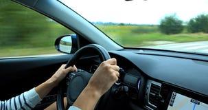 Las manos del ` s del conductor mienten en el volante de un coche a la velocidad en una carretera nacional Foto de archivo libre de regalías