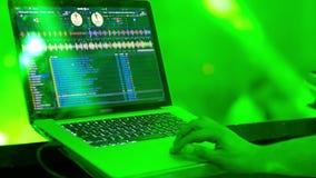 Las manos del ` s de DJ del hombre funcionan detrás de un ordenador portátil almacen de video